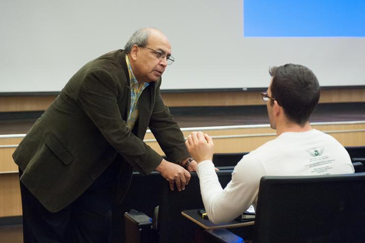 A photo of Ashok Goel instructing a male student in a classroom setting.
